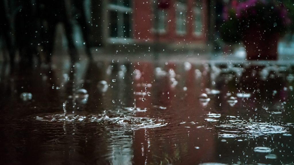 Raindrops falling on standing water in an area that needs custom drainage systems